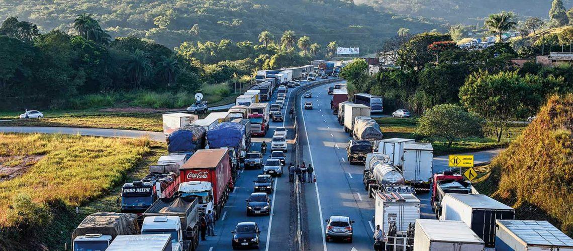 MG - GREVE/CAMINHONEIROS - GERAL - Caminhoneiros fecham a BR-262, em Juatuba, na Grande Belo Horizonte, nesta segunda-feira (21). De acordo com a AssociaÁ¿o Brasileira de Caminhoneiros, o protesto pede a reduÁ¿o de impostos, como os cobrados sobre o Ûleo diesel. A associaÁ¿o tambÈm critica os recentes reajustes no preÁo dos combustÌveis. A Petrobras disse que o valor acompanha as variaÁ¿es do mercado internacional. 21/05/2018 - Foto: DOUGLAS MAGNO/O TEMPO/ESTAD¿O CONTE¿DO
